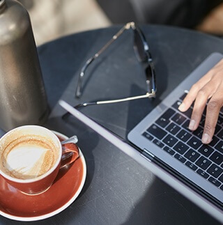 Persons using a laptop with a cup of coffee beside it